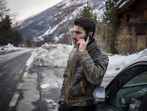 Young man talking on cellphone near car. Snowy road and mountain on background. Smiling man talking on cellphone with thumb up near car with open hood. Snowy royalty free stock image