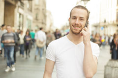 Smiling Man talking on mobile phone, city street Royalty Free Stock Photo
