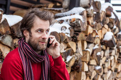Smiling man talking on a mobile phone outdoor during winter Royalty Free Stock Images