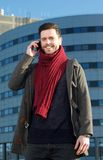 Smiling man talking on mobile phone outside building Royalty Free Stock Photography