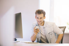 Smiling man talking on mobile phone while using laptop computer at desk in study. Stock Photos