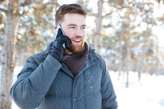 Smiling man talking on the phone in winter park Stock Images