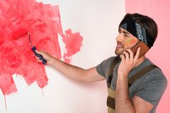 Smiling man talking on smartphone and painting wall in red by paint. Roller stock photos