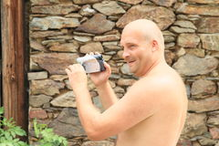 Smiling man taping with camera. Portrait of smiling young man with naked body taping video with camera Stock Photography