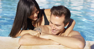 Smiling man with tattoo is cuddled by girlfriend Stock Photography