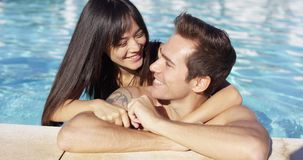Smiling man with tattoo is cuddled by girlfriend. While standing against the paved side of a swimming pool stock footage