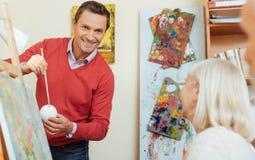 Smiling man teaching people in painting studio. Royalty Free Stock Image