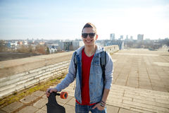 Smiling man or teenager with longboard on street Royalty Free Stock Photos