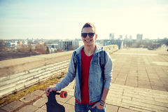 Smiling man or teenager with longboard on street. Sport, leisure, people and teenage concept - smiling young man or teenager with longboard on city street Stock Photography