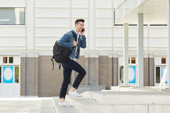 Smiling man on telephone call with backpack outside Royalty Free Stock Photo