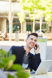 Smiling man on telephone call at cafe with laptop Stock Images