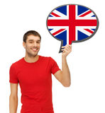 Smiling man with text bubble of british flag. Education, fogeign language, english, people and communication concept - smiling young man holding text bubble of stock image