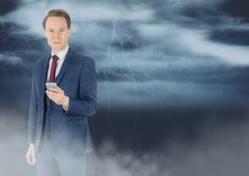Smiling man texting with lightnings in background Stock Photography