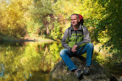 Smiling man in thought sits on a background of the  quiet river Royalty Free Stock Images