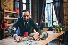 Portrait of mature man sitting at his desk in the office. Smiling man throwing money at desk in modern office. Enjoying being rich stock photos