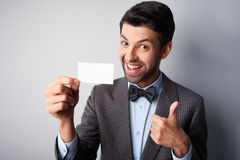 Smiling man with thumb up and blank visiting card Royalty Free Stock Photography