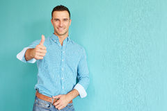Smiling man with thumb up. Happy man with thumb up on a turquoise background Royalty Free Stock Images