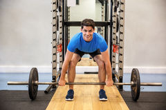 Smiling man about to lift a barbell Stock Photos