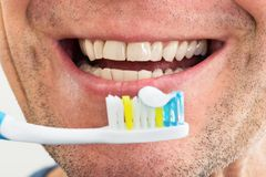 Smiling man with toothbrush Stock Photos