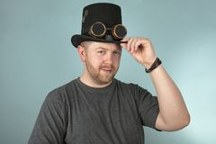 Smiling man in a top hat looking ahead. Serious young bearded man in a top hat looking solemnly at the camera over a grey studio background stock photo