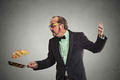 Smiling man tossing pancakes on frying pan Stock Photography