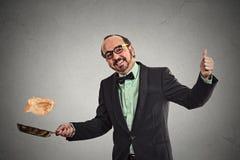 Smiling man tossing pancakes on frying pan Royalty Free Stock Photos
