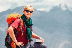 Smiling man tourist portrait with guide book on the mountain bac Royalty Free Stock Images