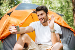 Smiling man tourist taking selfie with smartphone at touristic tent Royalty Free Stock Images