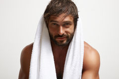 Smiling man with a towel after bath. Happy smiling man after bath. mancare Royalty Free Stock Image