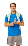 Smiling Man With Towel And Water Bottle. Portrait of smiling young man with towel and water bottle over white background. Vertical shot Royalty Free Stock Image