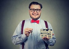 Smiling man with toy house and keys royalty free stock images