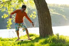 Smiling man is training on the balance board. Smiling bearded man is training on the balance board and having fun on a green meadow next to river on sunny Stock Photography