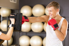 Smiling man training boxing at the fitness gym Stock Photos