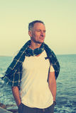 Smiling man traveler on the beach at the windy day Royalty Free Stock Image