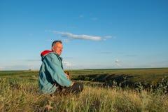Smiling man, traveler sits with a small dog among a green prairi Royalty Free Stock Photo