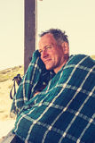 Smiling man, traveler sits, wrapped in a scarf Royalty Free Stock Photography