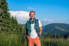 Smiling man traveler is standing on the alpine meadow Royalty Free Stock Photos