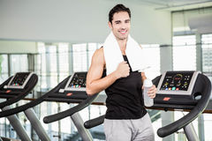 Smiling man on treadmill holding bottle of water Royalty Free Stock Photo