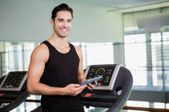 Smiling man on treadmill holding tablet Royalty Free Stock Images
