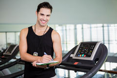 Smiling man on treadmill writing on clipboard Stock Images