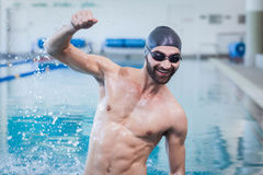 Smiling man triumphing with raised arm. At the pool Stock Photo