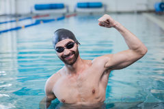 Smiling man triumphing with raised arm. At the pool Royalty Free Stock Photography