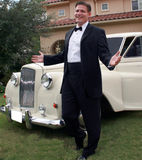 Smiling Man in Tuxedo. Man dressed in tuxedo stands next to classic limo, parked in front of upscale home, arms extended Stock Image
