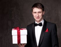 Smiling man in tuxedo with a gift box Royalty Free Stock Photo