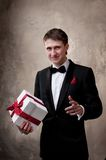 Smiling man in tuxedo with a gift box Royalty Free Stock Photos