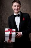 Smiling man in tuxedo with a gift box Royalty Free Stock Images
