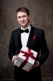 Smiling man in tuxedo with a gift box Stock Photo