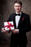 Smiling man in tuxedo with a gift box Stock Photography