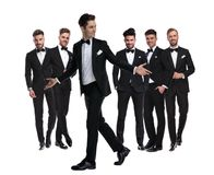 Smiling  man in tuxedo walks and welcomes while looking back stock images