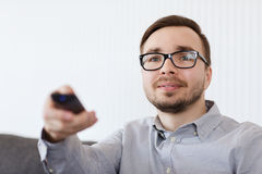 Smiling man with tv remote control at home Royalty Free Stock Images
